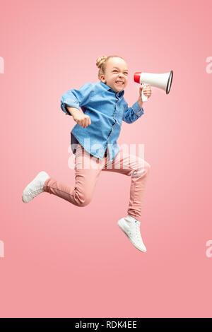 Belle jeune fille de l'adolescence de l'enfant sauter avec mégaphone plus isolé sur fond rose. Shining girl en mouvement ou mouvement. Les émotions humaines, les expressions du visage, concept publicitaire et