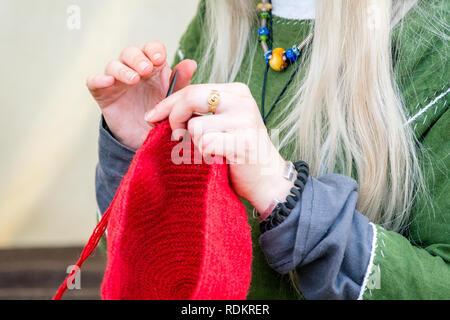 07f14a84afe0 ... Close-up of woman knitting mains chapeau en laine rouge, tout en  portant des
