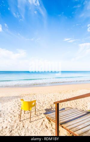 Passerelle en bois jaune et président sur plage déserte Banque D'Images