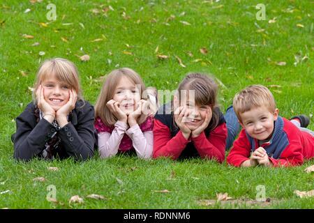 Quatre enfants se trouvant sur un pré Banque D'Images