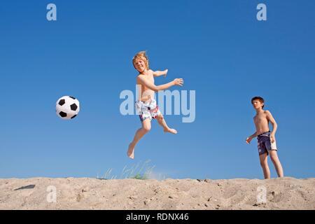 Deux jeunes garçons jouant avec un ballon de football sur une plage, l'île de Poel, Timmendorf, Mecklembourg-Poméranie-Occidentale, Allemagne du Nord Banque D'Images