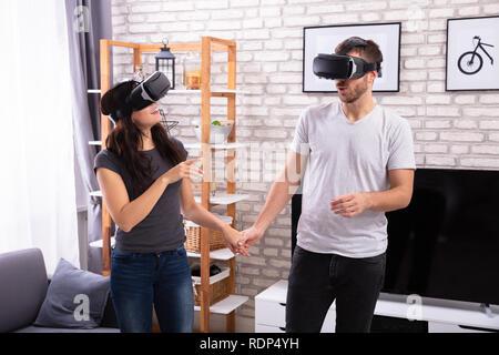 Jeune couple à l'aide de périphériques de réalité virtuelle à la maison Banque D'Images