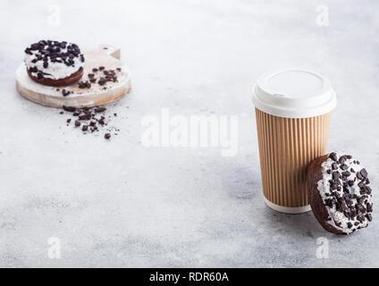 Tasse à café en carton noire avec cookies donuts sur l'arrière-plan de table de cuisine en pierre. Boire un Café et collation. Banque D'Images
