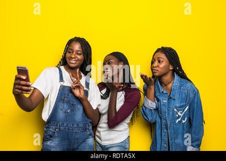 Trois belles femmes africaines dans les tenues de prendre un air de soufflage baisers avec selfies isolés téléphone mobile sur fond jaune Banque D'Images