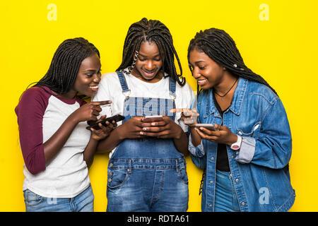 Trois belles femmes africaines utilisent le téléphone mobile partager actualités sur fond jaune isolé Banque D'Images