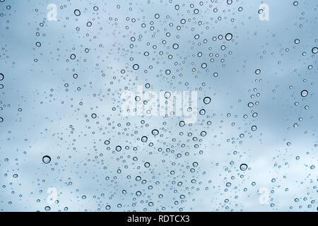 Gouttes de pluie sur le pare-brise; à l'arrière ciel nuageux, en Californie Banque D'Images