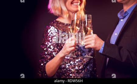 Image de l'heureux couple avec verres de champagne avec champagne sur fond noir Banque D'Images