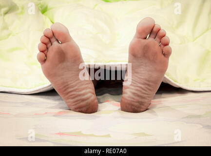 Pieds d'un homme endormi qui sort de sous la couverture. Banque D'Images