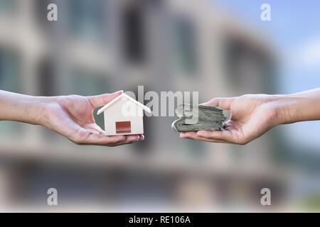 Maison de prêt, hypothèque, endettement, concept de l'achat d'une maison. Main tenant petit échange résident sur l'argent flou en arrière-plan de l'immobilier. L'échange d'un financement