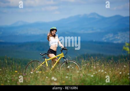 Happy young woman rider avec vtt jaune souriant pour l'appareil photo, showing Thumbs up, le port de casque, debout sur un jour d'été à l'herbe. Montagnes, ciel bleu sur l'arrière-plan flou. Copy space Banque D'Images