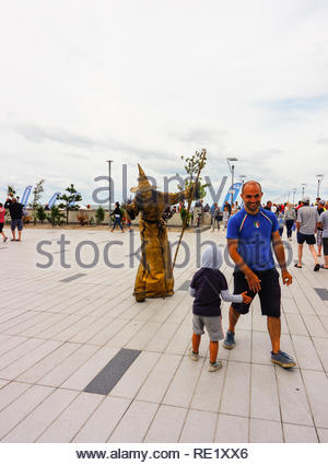 Kolobrzeg, Pologne - 10 août 2018: Man and boy marche loin de.une personne habillée en sorcière en vêtements d'or a proximité de la plage sur une journée nuageuse. Banque D'Images