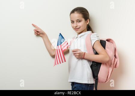 Enfant de l'école avec un sac à dos tient le drapeau américain, l'arrière-plan lumineux mur dans l'école, point avec votre doigt emplacement de copy space Banque D'Images