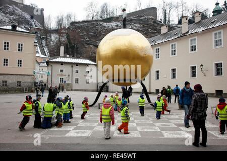 """Groupe de maternelle sur un voyage sur la Kapitelplatz square au 'Sphaera"""" sculpture de Stephan Balkenhol, Salzbourg, Autriche Banque D'Images"""