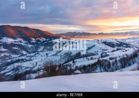 Lever du soleil d'hiver dans les montagnes des Carpates. belle campagne. le ciel est en feu. zone rurale avec des collines. bonjour monde merveilleux Banque D'Images