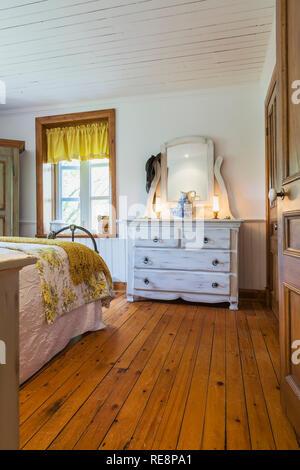 Vue partielle de king size avec couvre-lit fleuri blanc et jaune de couleur crème, finition antique vaisselier en bois dans la chambre à coucher principale dans la vieille maison Banque D'Images
