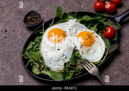 Deux œufs frits, Sunny Side Up, le pan avec des herbes, roquette, épinards, tomates cerise et poivre, avec une fourchette d'un fond brun. Concept de vie sain Banque D'Images