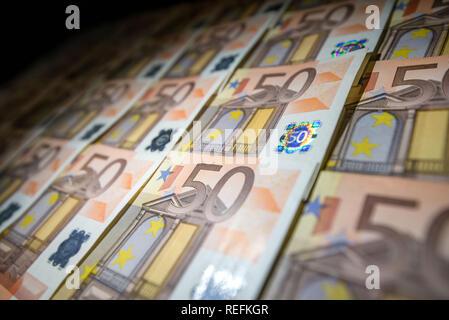 50 euro l'argent de papier sur fond noir. Des centaines de billets. Notion de flux de trésorerie, les finances, les gens riches, millionnaire et réussite de l'entreprise.