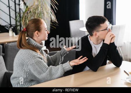 Malheureux jeune couple arguing, épouse en colère à la recherche de mari lui reproche de problèmes, les conflits dans le mariage, de mauvais rapports, l'homme et la femme ayant disputé ou désaccord