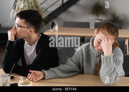 Malheureux en colère jeune couple ignorant de ne pas regarder après la lutte ou se querellent, bouleversé les conjoints réfléchie en évitant de parler, assis silencieusement sur la table, ayant des problèmes de relation Banque D'Images