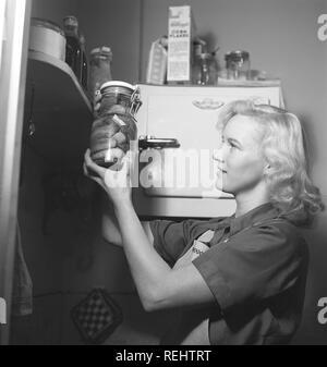 1940 conseils pratiques. Une jeune femme à l'air heureux lors de la tenue d'une bouteille en verre avec des concombres conservés. Elle est dans la cuisine vêtu d'un tablier. L'année est 1940 et la seconde guerre mondiale est en cours. La nourriture et autres nécessités sont rationnés, donc un propre approvisionnement de nourriture était nécessaire. Kristoffersson 157-24 Photo Banque D'Images