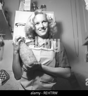 1940 conseils pratiques. Une jeune femme à l'air heureux lors de la tenue d'une bouteille en verre avec des fruits conservés. Elle est dans la cuisine vêtu d'un tablier. L'année est 1940 et la seconde guerre mondiale est en cours. La nourriture et autres nécessités sont rationnés, donc un propre approvisionnement de nourriture était nécessaire. Kristoffersson 157-23 Photo Banque D'Images