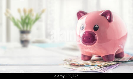 Tirelire Comité permanent sur les billets en euros sur la table dans l'intérieur de la famille. Le concept de la banque, assurance et services financiers pour les membres de la famille et hous