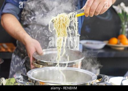 Chef sort avec une cuillère perforée à la vapeur chaude de nouilles aux oeufs de la poêle Banque D'Images