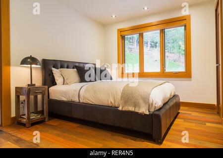 Lit King size avec panneau en cuir brun tête de lit et les tables de bout en bois lumineux avec lampes en guest chambre avec parquet en bois de chêne dans la maison de luxe Banque D'Images