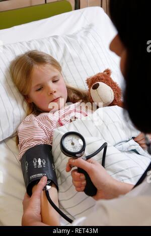 La mesure de la pression artérielle infirmière d'un jeune patient, 7 ans, à l'hôpital Banque D'Images