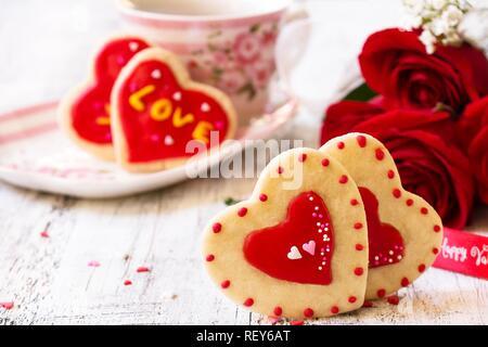 Des Guns N Roses roses rouges cookies café cupof sur fond blanc rustique, selective focus Banque D'Images