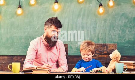 Enseignant et petit enfant d'écrire des lettres en cahier. Cute boy un dessin avec des crayons de couleur. Leçon d'art à l'école maternelle
