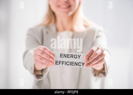Selective focus female hands holding card sur fond blanc, de l'efficacité énergétique concept Banque D'Images
