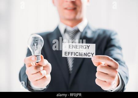 Carte de mise au point sélective et lampe à DEL dans les mains des hommes d'affaires sur fond blanc, de l'efficacité énergétique concept Banque D'Images