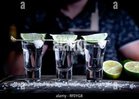 Apéritif entre amis dans le bar, trois verres d'alcool avec de la chaux et du sel pour la décoration. Tequila shots, selective focus Banque D'Images