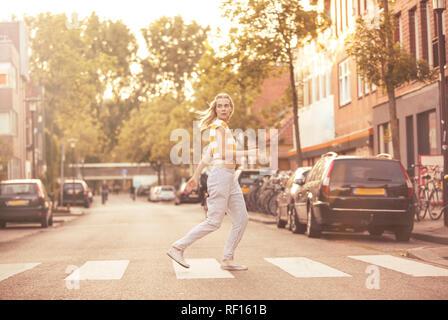 Young woman walking on zebra crossing