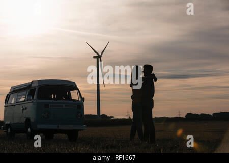 Couple au camping-van au crépuscule avec wind turbine in background Banque D'Images