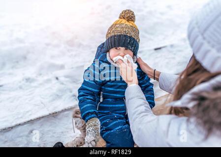 Lingettes maman télécharger fils assis sur un banc dans le parc d'hiver. Soin d'une jeune mère d'un enfant est un garçon. Le concept d'un écoulement nasal et la congestion nasale chez les enfants en hiver.