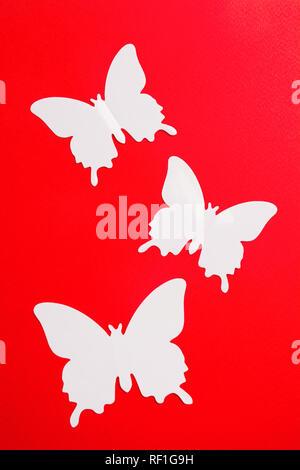 Fond d'été avec papillon en plastique rouge sur fond de papier, mise à plat, vertical style shot Banque D'Images
