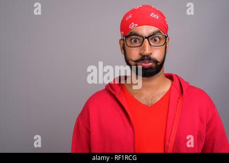 Ennuyer Indian man wearing red shirt et faire drôle de visage Banque D'Images