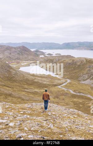 Les jeunes d'amn debout sur une colline, surplombant le lac Inari, Finlande Banque D'Images