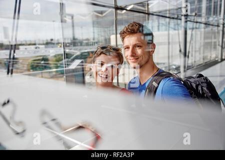 Portrait of smiling couple à l'aéroport à la fenêtre de Banque D'Images
