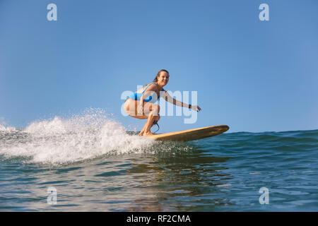 L'INDONÉSIE, Bali, Batubolong beach, femme enceinte, surfer dans l'océan Banque D'Images