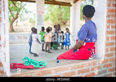 Un enseignant veille sur sa classe de jeunes enfants dans un milieu rural, École ouverte prix près de Chikwawa, Malawi. Banque D'Images