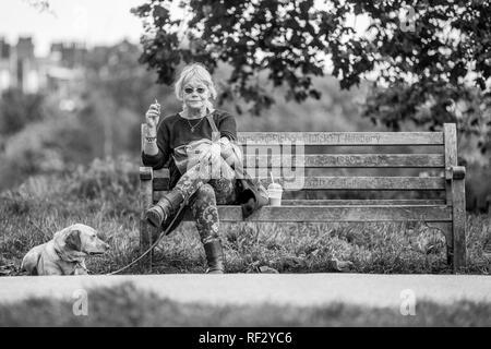 Une femme assise sur un banc de parc et son chien attendent pour entrer une exposition canine