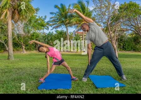 Père et fille l'importance de l'étirement latéral dans le cadre des exercices matinaux. La petite fille se débat pour atteindre autant que papa. Banque D'Images