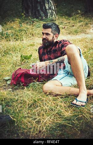 Chemise à carreaux en tourisme tenir mug. Hipster avec longue barbe et vous détendre sur l'herbe verte. Homme barbu avec thé ou café tasse en forêt. Camping, boire du café et de l'humeur. Concept de vacances d'été Banque D'Images