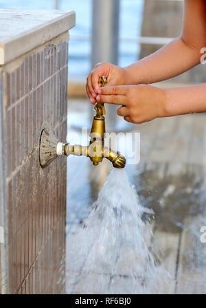 Close-up kid mains ferme le robinet. Old grunge touchez dans jardin Banque D'Images