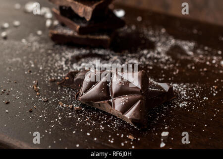 Morceaux de chocolat amer à la fleur de sel sur la surface en bois sombre. Des collations bio.
