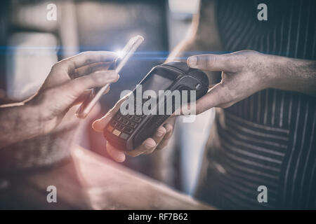 Femme de payer bill par smartphone à l'aide de la technologie NFC Banque D'Images