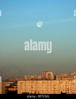 Le disque de la lune sur la ville, tôt le matin à l'aube. Instantané avec lumière naturelle. Banque D'Images